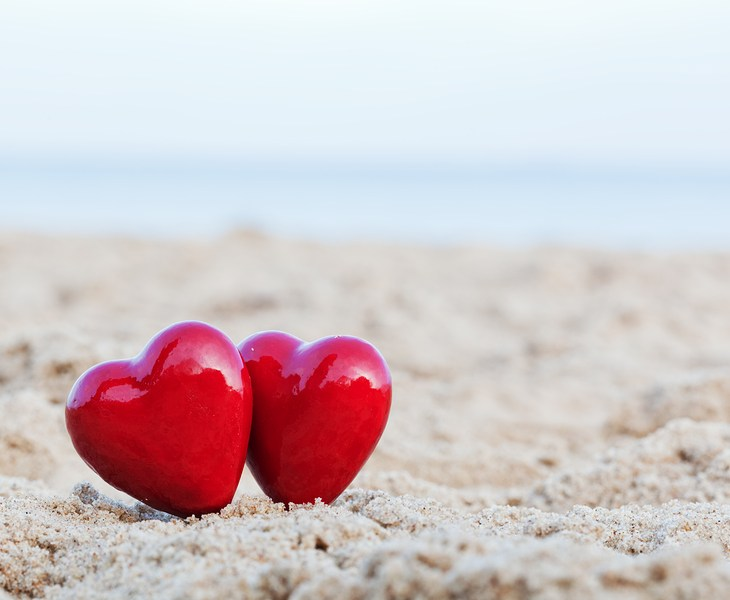 Two red hearts on the beach symbolizing love, Valentine's Day, r